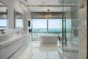 En suite with white tile floor, white cabinets, ceiling and walls, white marble countertop; glass shower on right; white freestanding soaker tub straight ahead, with large windows behind and chandelier above