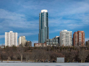 Exterior shot of circular condo tower, with blue windows and white roof, from a distance, in winter; leave-less trees in foreground; shorter white and brick condo buildings on either side