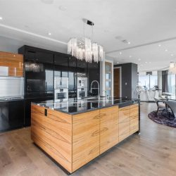Interior kitchen-dining area; hardwood floor and island with black marble top and sink, chandelier overhead; black cabinets, white ceiling