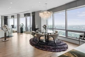 Interior penthouse rounded living room with hardwood floor and large windows; small black dining table with six white cloth chairs around it, on top of purple shag carpet, white chandelier overhead; white ceiling, light grey walls and curtain