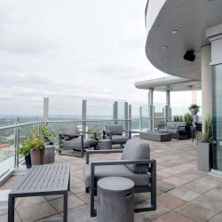 Penthouse curved patio with light grey and red stone floor on left, white building on right; dark grey cloth chairs and green potted plants throughout