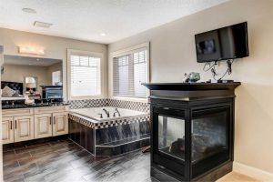En suite bathroom with dark floors, corner bathtub, three-sided fireplace and wall-mounted TV