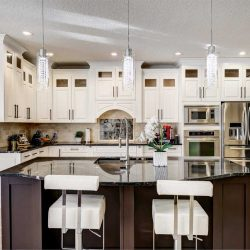 Kitchen with white cabinets, three lights hanging over black island with white chairs