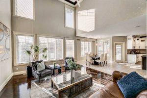 Interior living room-kitchen open concept with white walls; dark hardwood floor with brown furniture in living room, white tile floor and dining chairs in kitchen