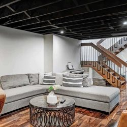 Black, uncovered ceiling, wood floor and grey sectional couch.