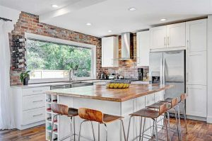 White kitchen island with wood chairs; white cupboards, large window with brick border.