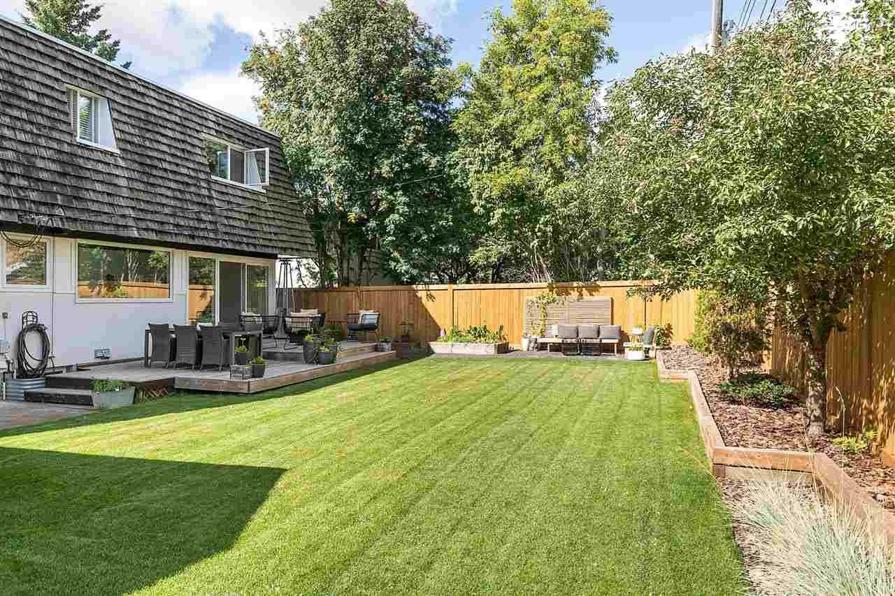Long, green lawn and ground-level patio in yard surrounded by trees.