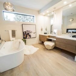 Interior en suite bathroom with white oak floor, white ceiling and walls; his-and-her sinks above brown wood drawers on the right; rectangular window at head height on back wall; white soaker tub against two-way fireplace on the left