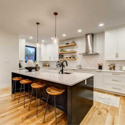 Kitchen with white ceiling and walls, light hardwood floor; black-base island with light grey top and black faucet in sink and two lights hanging above, four wood-seat stools; white cupboards and pantry