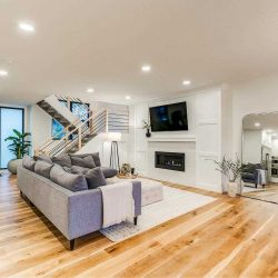 Interior living room, white ceiling and walls, light hardwood floor; grey sectional couch facing right to TV mounted above fireplace; open-air stairs background to the left; large mirror against the wall to the right