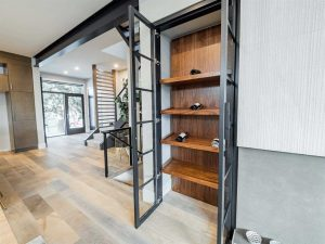 Interior shot of wine rack with entrance to the left in the background; black-framed glass doors open to mostly empty four-shelf wood wine rack; white oak floors lead to entrance; black beam on white ceiling