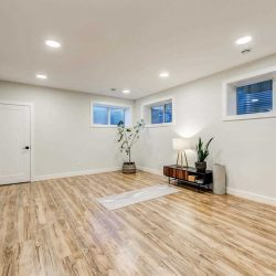 Basement yoga studio with white ceiling and walls, light hardwood floor and a white yoga mat; small table against wall with lamp and plant on top; three ground-level windows on the middle and right; plant in the corner