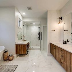 En suite bathroom with white ceiling and walls, light hardwood floor; wood cupboards and large mirror on right; glass shower in background with wood makeup counter with round mirror in front; white soaker tub to the left