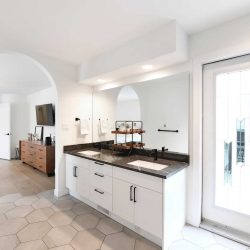 En suite bathroom sinks with bedroom visible through arched entranceway; light tile floor, white ceiling and walls; patio door on right
