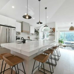 Interior kitchen, light hardwood floor, white island, cupboards, walls and slanted ceiling; three lights hanging over white marble island with six stools around it