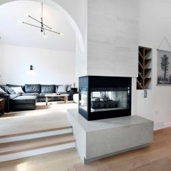 Risen living room through arched entrance with three-sided fireplace on the right; light hardwood floor, white ceiling and walls; section black couch around small wood fireplace and plant on the left