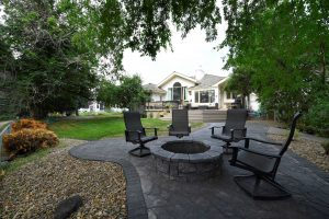 Backyard view from dark grey stone fire pit with four chairs surrounding it and trees on either side; lawn leading to deck and house