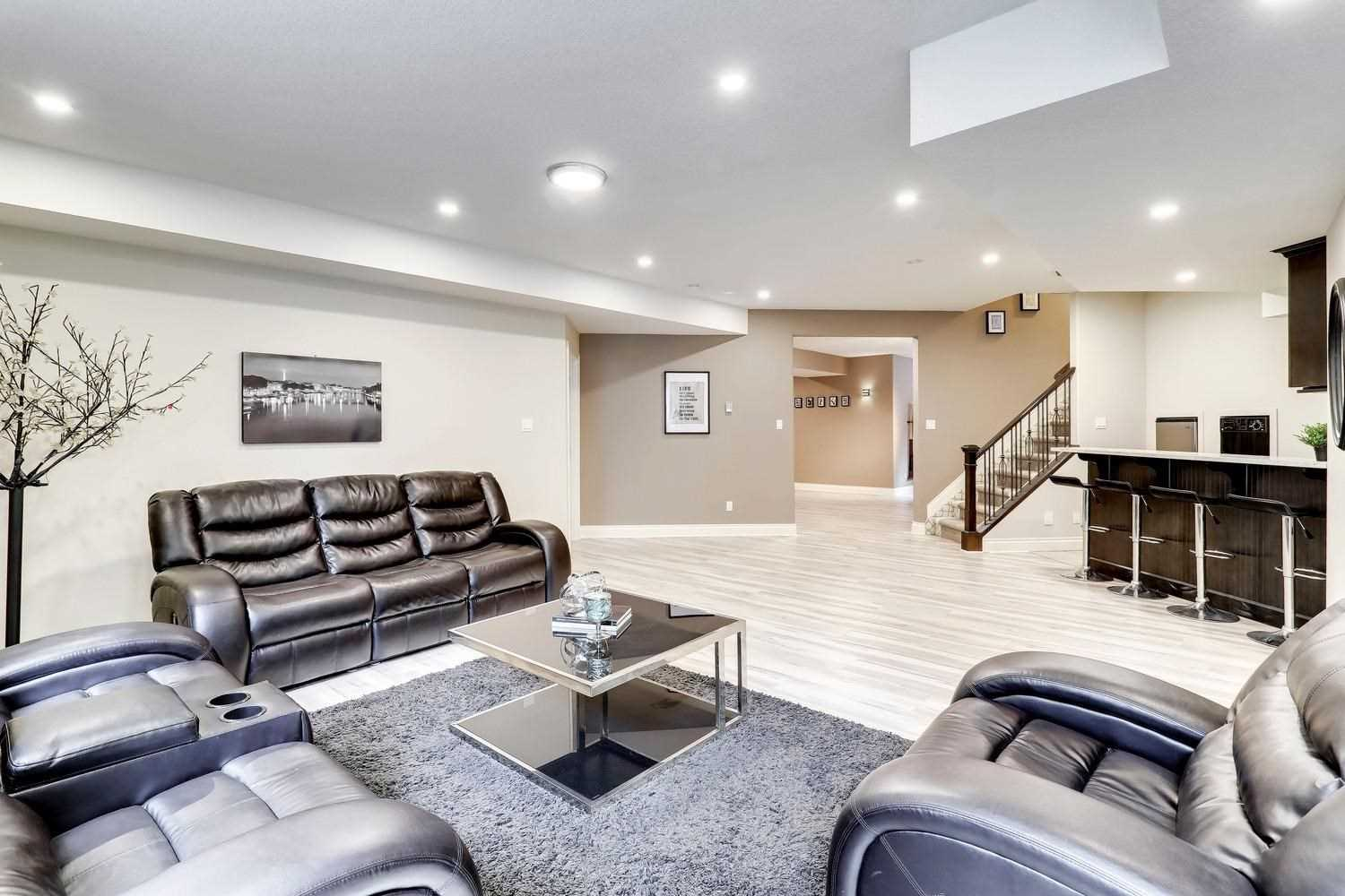 Basement with white ceiling and walls; leather couches surrounding glass and steal coffee table on three sides, on top of dark grey shag carpet; four stools in front of bar to right, wood railing stairs in background