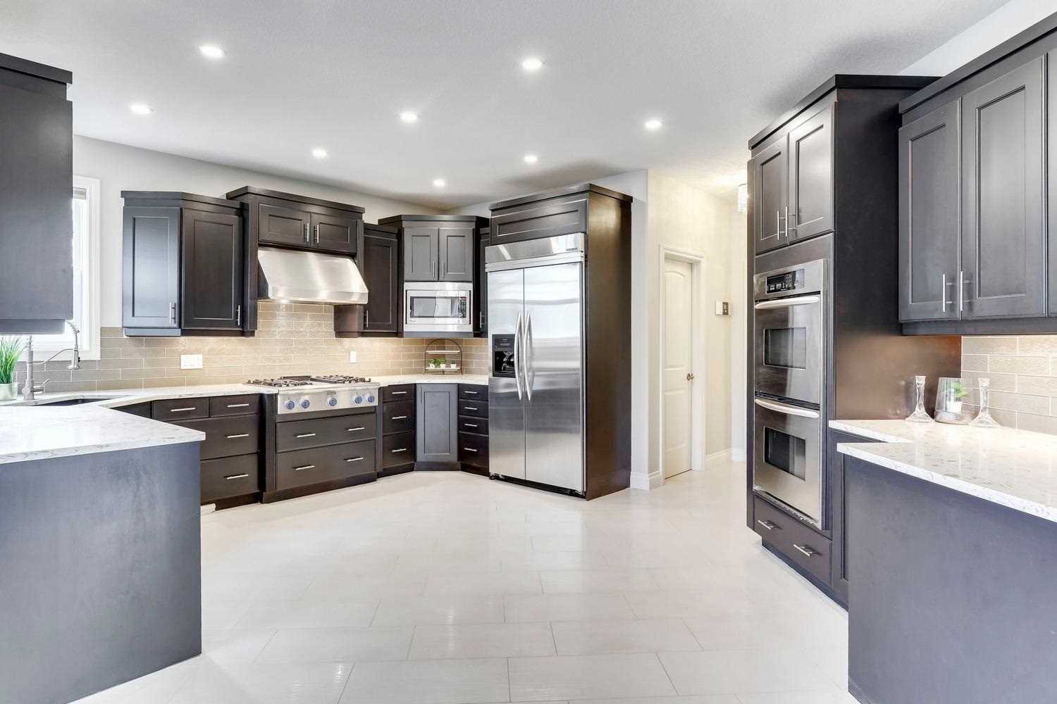 Kitchen with white ceiling and tile floor; dark brown cupboards and cabinets