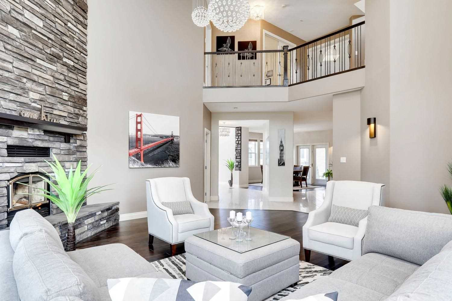 Living room, dark hardwood floor, white ceiling and walls; white sectional couch with white chairs around grey cloth coffee table; dark grey brick fireplace to left