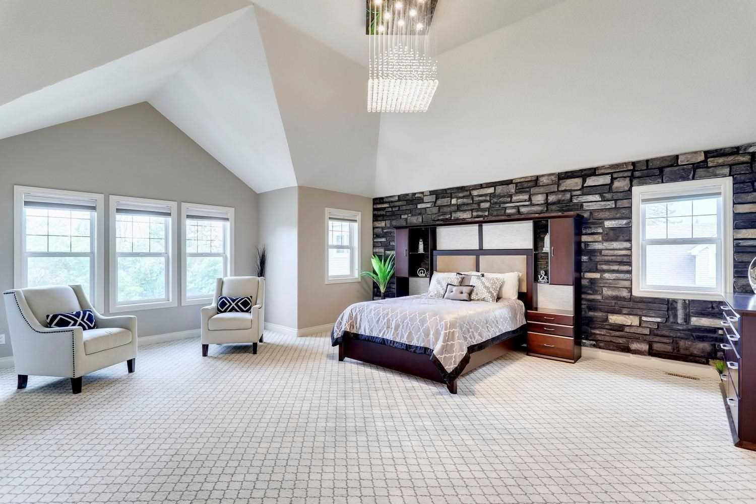 Master bedroom with white carpet, ceiling and walls; dark grey brick feature wall behind bed with cabinets built in to frame; two white chairs in front of windows to left; glass chandelier above