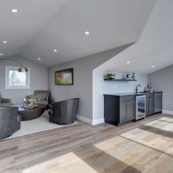 Upstairs loft, white ceiling and walls, light hardwood floor; four black chairs to left around half-sphere coffee table; small sink, mini-fridge and washer to right