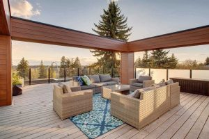 Rooftop patio with wood plank floor; beige and grey wicker couches and chairs around beige wicker coffee table; wood beams making a rectangle above, glass rail around floor; pine tree in background