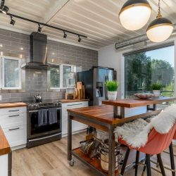 Interior seacan kitchen, light hardwood floor, white ceiling and wall, light grey back splash; rolling kitchen island, hardwood countertops, white cupboards and drawers