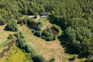Overhead view of black seacan home and land with two small ponds surrounded by trees