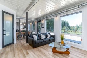 Seacan living room, white walls, silver ceiling light hardwood floor; black leather couch in front of wood-based, glass top coffee table; glass door to left, large windows and glass exterior door to right
