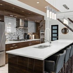 Black kitchen island with white counter, six chairs on right side, two sets of four lights hanging above; dark brown cabinet, black and white tile backsplash, silver fridge on left, stairs on right