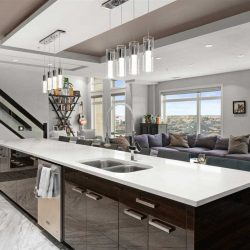 Interior kitchen-living room, white marble kitchen floor, dark hardwood living room floor; black island with white counter in foreground, two sets of four lights hanging above; large grey sectional in front of large windows in background; stairs to the left
