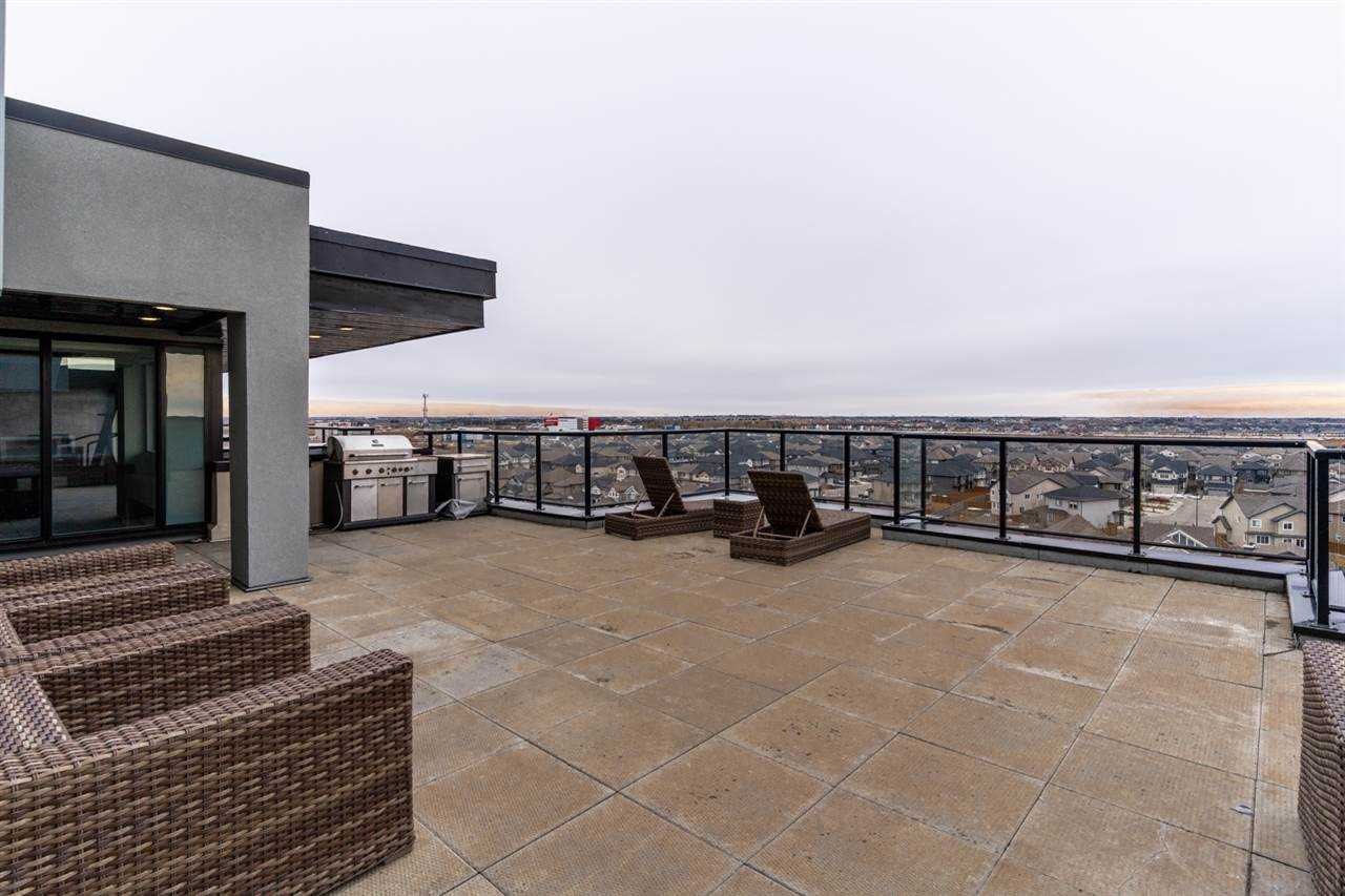 Rooftop patio, brown cement floor, brown wicker furniture, grey building entrance with BBQ on left; glass railing and open sky to right