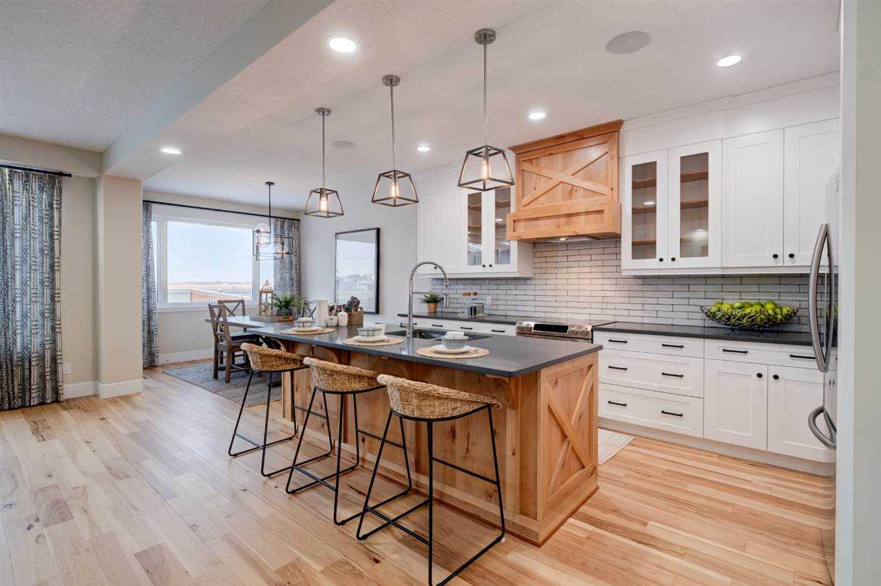 Kitchen, with white ceiling and light wood floor; light wood base for kitchen island with three lights hanging over it; white cabinets