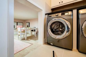 Laundry room, with grey and silver clothes dryer, opening to a half-height kids' crawl space with tea party decor