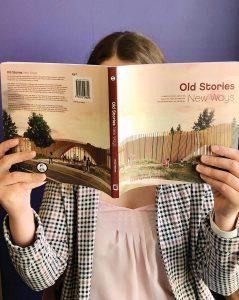 Stage_HoldingUpBook_OldStoriesNewWays