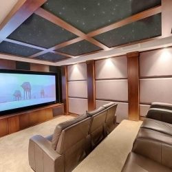 Interior movie room with wood coffered ceiling, stadium seating with grey recliners; Star Wars' AT-AT Walkers on screen