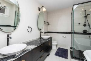 Interior en suite bathroom; white floor and walls, two sinks with single faucets and round windows above; stand-up glass shower and soaker tub on the right