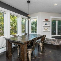 Interior dining room, dark wood floor and table, silver steel chairs, white windows and walls, hanging Edison lightbulb over the table, dark stone fireplace
