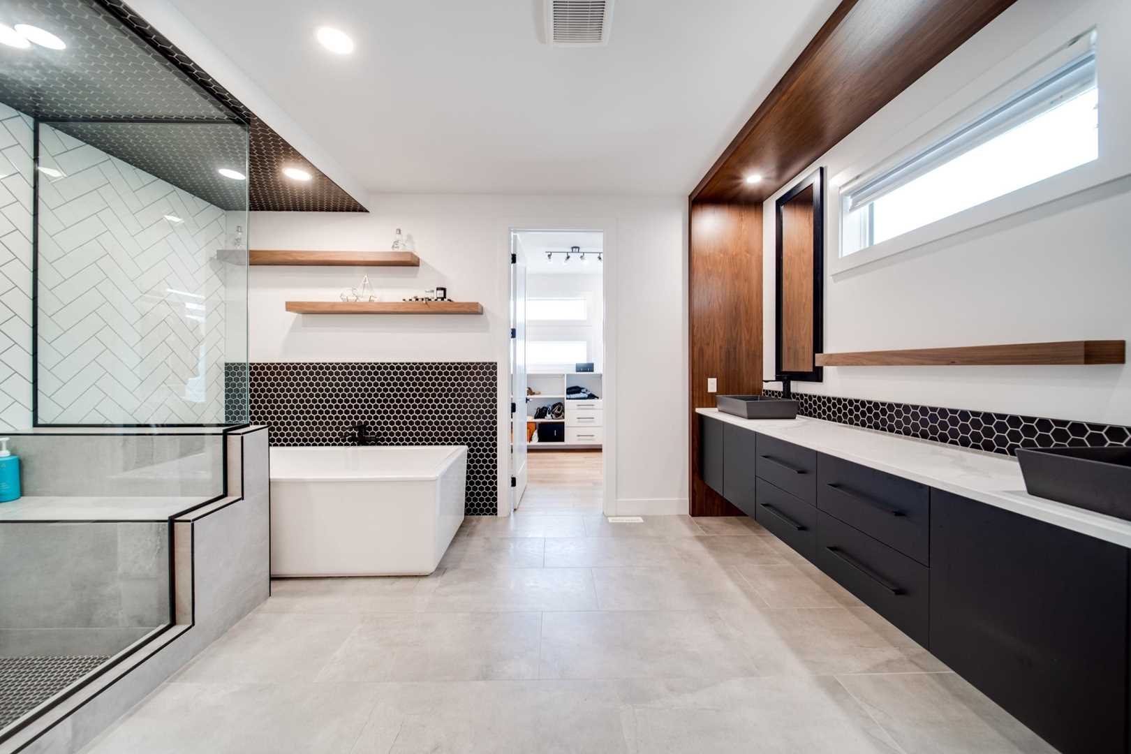 En suite bathroom, white ceiling and walls, light hardwood floor; large mirror over white counter and black cupboards on right; shower and soaker tub on left