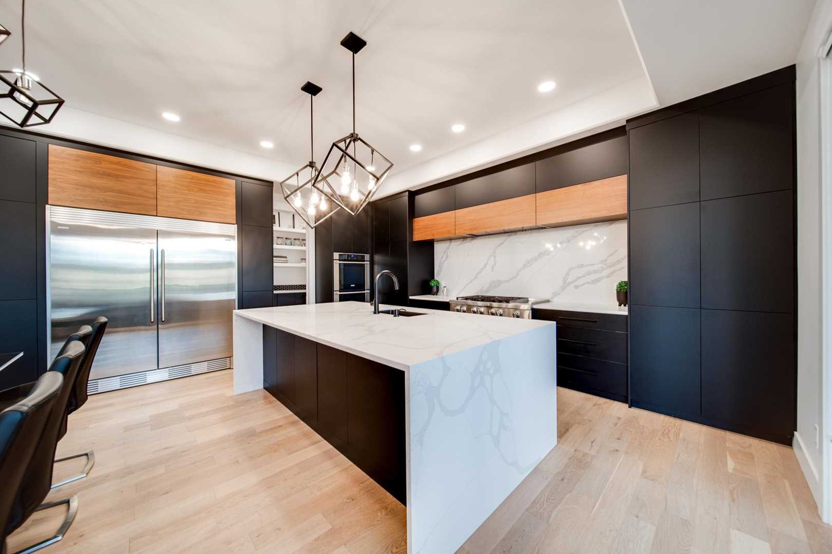 Kitchen with white ceiling and walls, light hardwood floor; black cupboards with white backsplash; white marble waterfall island with two hanging geometric lights above