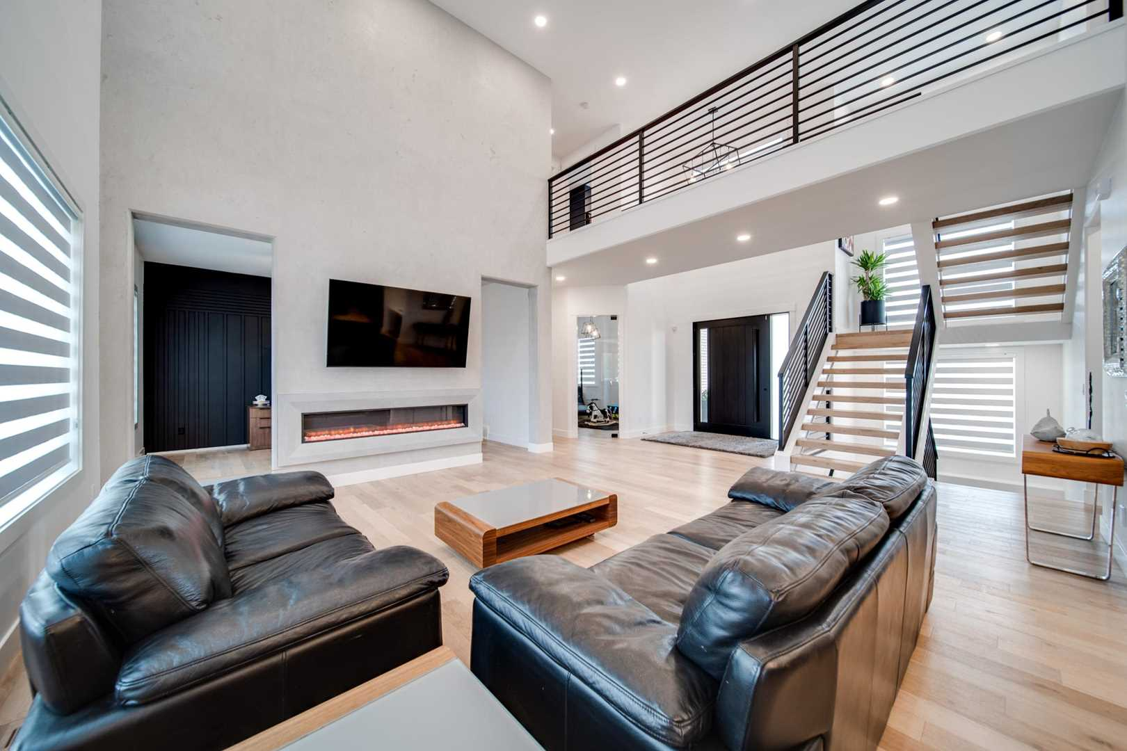Interior living room, white ceiling and walls, light hardwood floor; two black couches in foreground in front of wood coffee table, facing wall-mounted TV; open air stairs to right