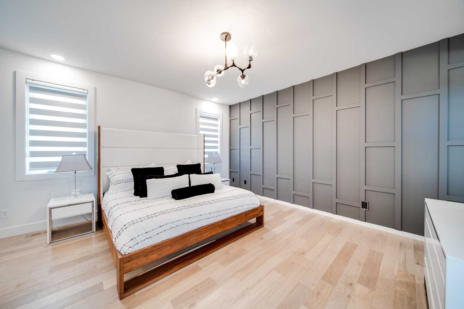 Master bedroom, white ceiling and walls, light hardwood floor; grey textured feature wall on right; geometric light above white bed with wood frame