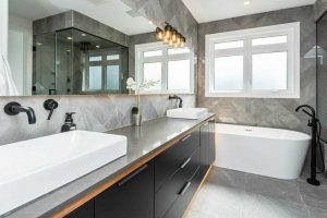En suite with grey tile floors and walls, white ceiling; two separate sinks on left above black cabinets and below full size mirror; white tub with black faucet to the right below window