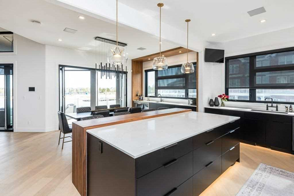 Kitchen with white ceiling and walls, light hardwood floor; black cabinets and drawers, including on island with white counter and wood extension and three hanging lights above; sink to the right, with windows and small TV above; dining table beyond kitchen area