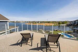 Rooftop deck, light brown floor with glass railing; two black and beige recliner deck chairs looking out to lake with neighbour homes and pool to the right