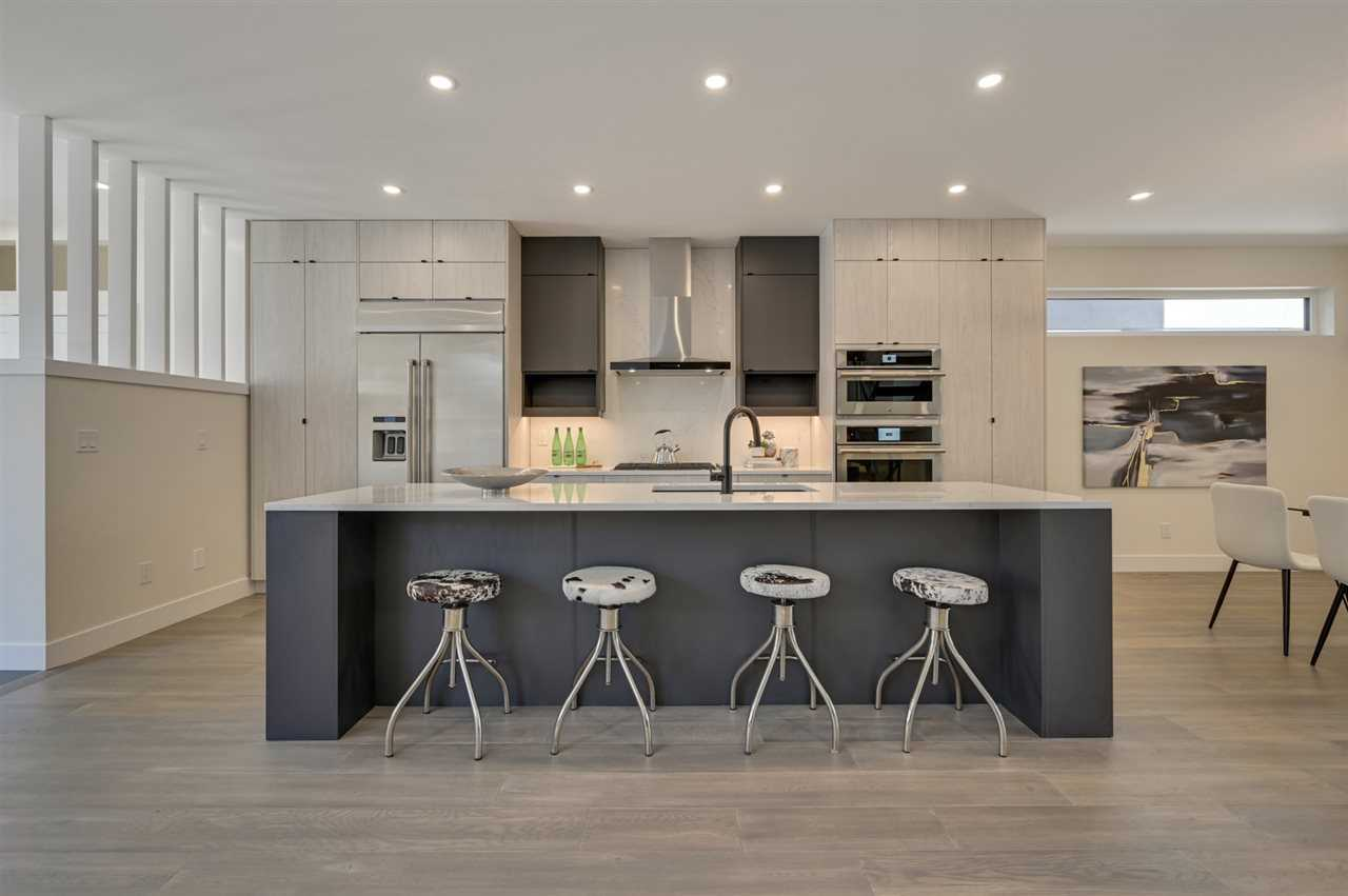 Interior kitchen with grey hardwood floor and white ceiling with embedded circular lights; black base island with white top (and sink) and room to slide four stools under its overhang; light grey cabinets with two black shelves on either side of hood fan above stove