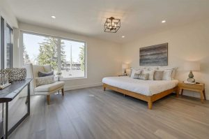 Master bedroom with grey hardwood floor, white ceiling (with small, box-framed light in middle) and walls; large bed with white covers on wood frame, wood night stand beside; white chair in front of large windows to the left
