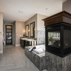 En suite bathroom with three-sided fireplace, light marble floor, wood shelving, large tub and his-and-her sinks