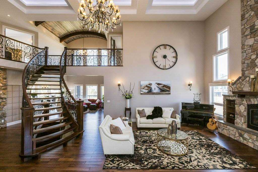 Two-storey living room with white walls and coffered ceiling skylights; large windows beside dark brick fireplace extending to ceiling; iron spindle hardwood staircase next to chandelier leading to second floor